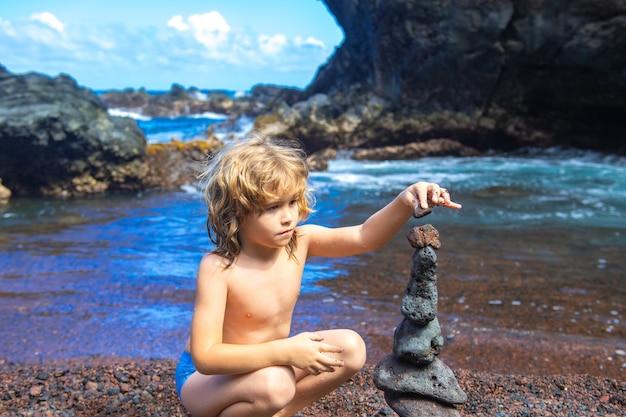 자연 속에서 바다의 해안에 스택 돌을 만드는 귀여운 꼬마 소년. 바다 해변의 케른, 5개의 자갈 타워. 균형과 조화의 개념입니다. 평온과 정신.