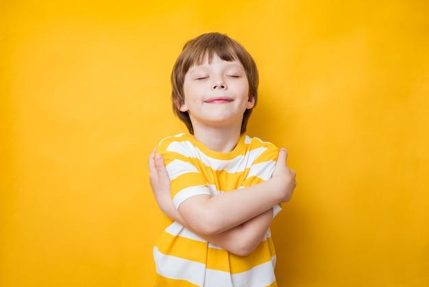 抱きしめながら、肩に腕を組んで喜んで笑うかわいい男の子。ボディポジティブ、自己受容、自尊心の概念