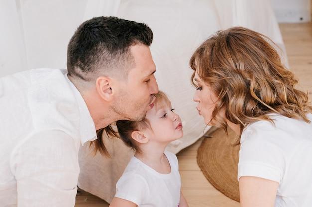 Милый ребенок, дочь и папа щекочут маму, весело проводят время, играя вместе дома, счастливые родители и девочка маленького ребенка наслаждаются забавной деятельностью и общением, семья смеется, расслабляется