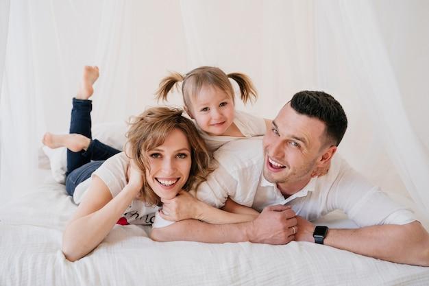 かわいい子供娘とお父さんくすぐりママが家で一緒に遊んで楽しい時間を過ごして、幸せな親と面白い活動とコミュニケーション、リラックスして笑って家族を楽しんでいる子少女