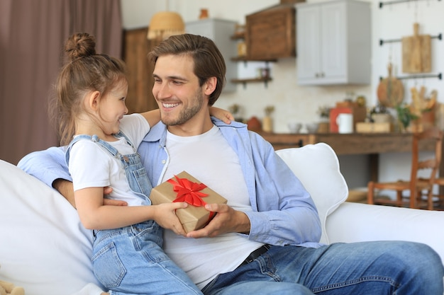 귀여운 딸은 아빠를 놀라게 하고, 어린 소녀는 소파에 앉아 있는 아빠에게 선물 상자를 선물합니다. 아버지의 날.