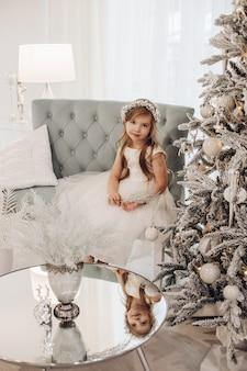 그녀의 손에 작은 지점을 가지고 노는 흰색 옷을 입고 귀여운 아이
