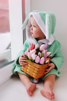 Cute kid in an easter bunny costume with a bouquet of flowers sits on a window sill against the window and smiles.