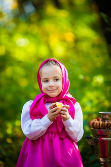 Милая девочка в розовом платке и платье, в белой куртке, как маша и медведь из мультика.