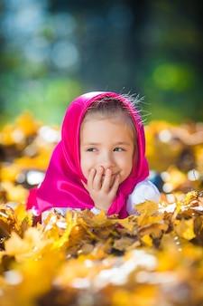 Una ragazzina carina con uno scialle e un vestito rosa, una giacca bianca come masha e l'orso del cartone animato.