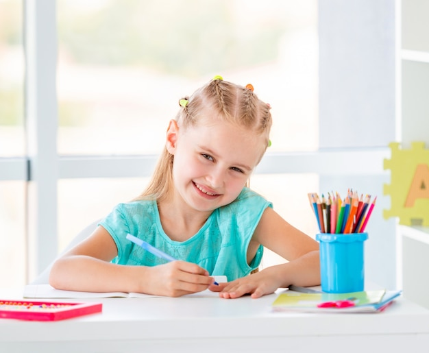 Cute kid girl sitting at the desk, coloring with pencils