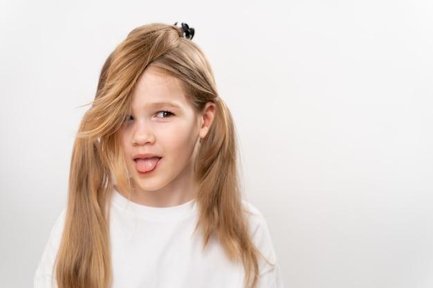 面白い収集された髪と舌が白に突き出ているかわいい子供の女の子