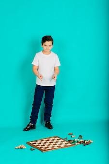 Милый ребенок держит на руках партию в шахматы,