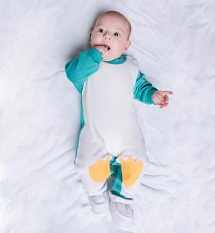 Милый ребенок в костюме пингвина, лежащий на одеяле