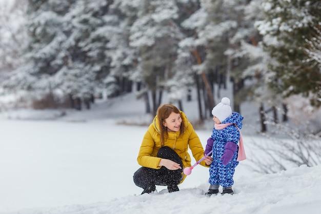 Милый ребенок в теплой одежде веселится на свежем воздухе с мамой и дочерью семейный отдых и досуг