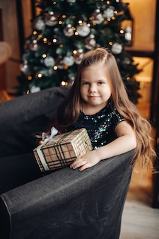 Cute kid little girl with long hairs sitting in armchair holding festive xmas gift on of christmas tree.