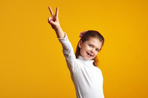 Милый ребенок делает жест мира с поднятой рукой у желтой стены