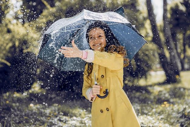 Bambino carino plaiyng in una giornata piovosa