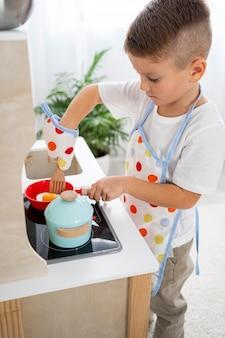 Ragazzo carino che gioca con un gioco di cucina