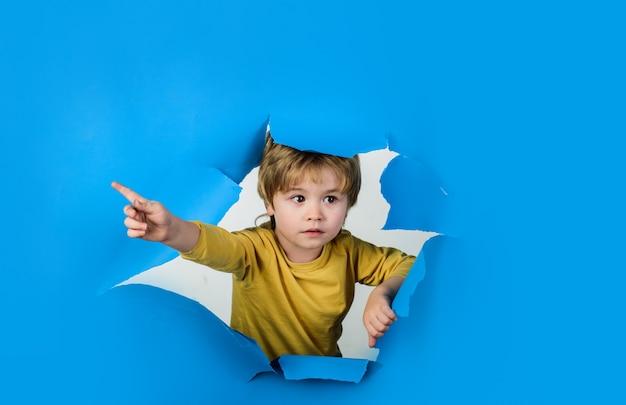 指で指しているかわいい子供は、紙の穴の広告バナーを覗いて驚いた子供をのぞきます