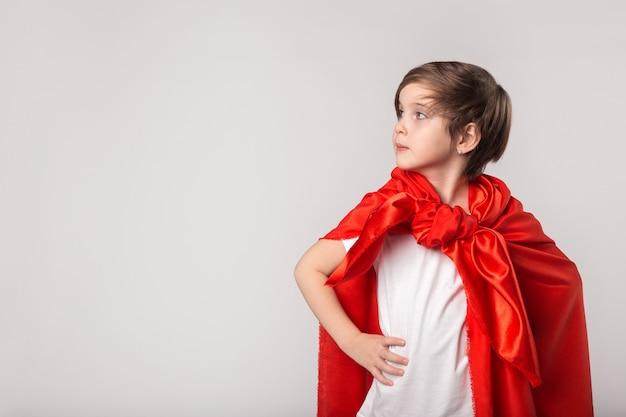 Cute kid pretend superwoman in studio