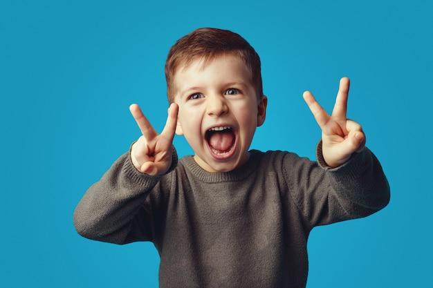 Милый ребенок поднимает руки, показывает жест мира с открытым ртом, счастливо смеется
