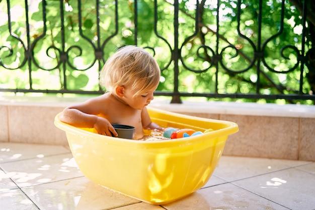 귀여운 아이는 물이 담긴 그릇에 앉아서 장난감을 봅니다.