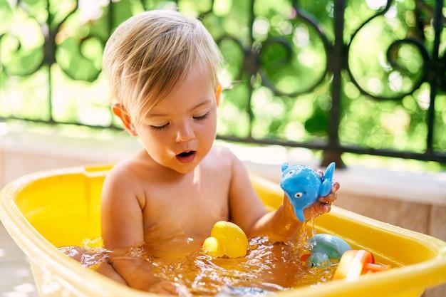 귀여운 아이는 물이 담긴 그릇에 앉아서 장난감을 가지고 노는다