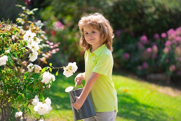 여름날 정원에서 꽃에 물을 주는 귀여운 꼬마. 여름날 물뿌리개를 사용하는 아이. 작은 도우미.