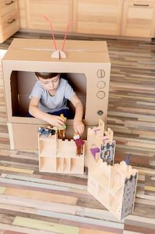 Cute kid with cardboard tv high angle