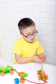 다운 증후군이있는 귀여운 아이가 유치원에서 놀고 있습니다.