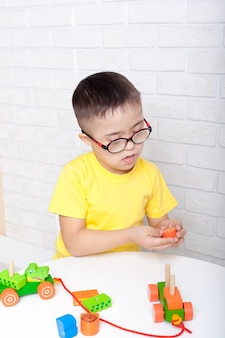 Cute kid with down's syndrome playing in kindergarten.