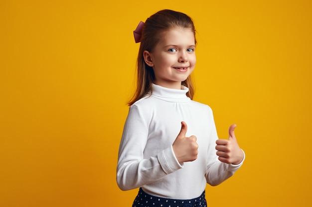 Милый ребенок с открытым ртом показывает палец вверх изолирован на желтой стене