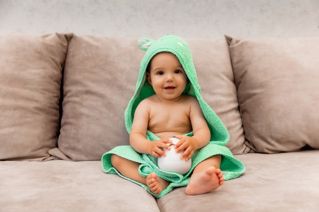 A cute kid wrapped in a towel sits on the bed. baby in a bath towel.