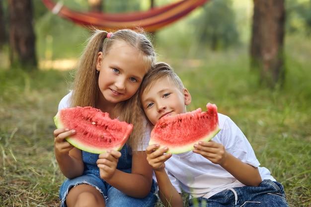 庭でスイカを食べるかわいい子供たち。