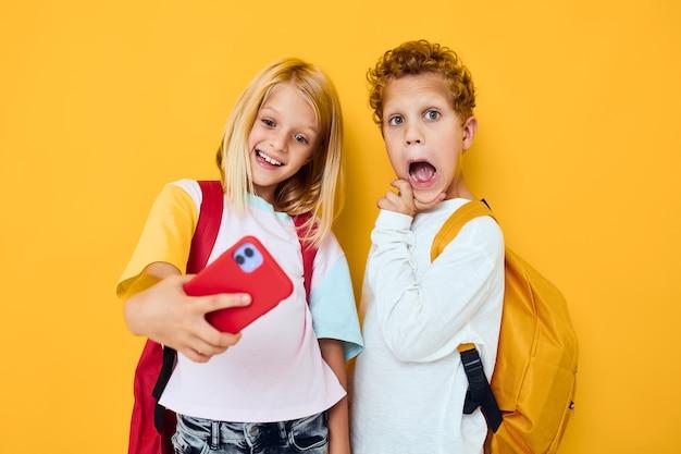 かわいい子供たちの電話selfieしかめっ面楽しいスタジオ教育の概念