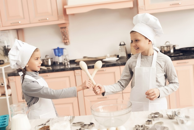 Cute kids play wooden spoons swords at kitchen.
