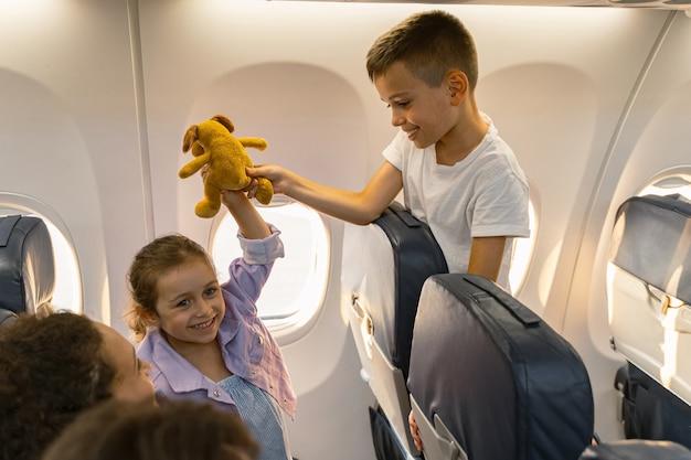 Симпатичные дети играют на борту самолета у окна