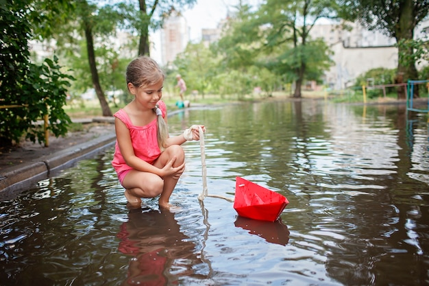Cute kids playing with paper boat in the puddles after warm summer rain happy childhood