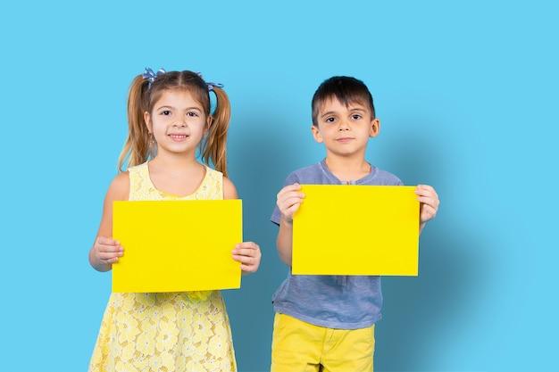Симпатичные дети позируют с подсветкой цветного бланка для вашей рекламной фотографии на синем изолированном фоне