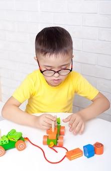 탁아소의 책상에 앉아 장난감을 개발하고 노는 특별한 도움이 필요한 귀여운 아이들.