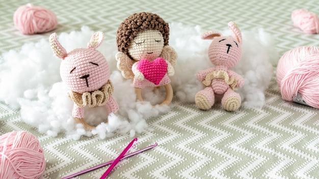 Simpatici giocattoli di peluche lavorati a maglia sul divano con peluche intorno