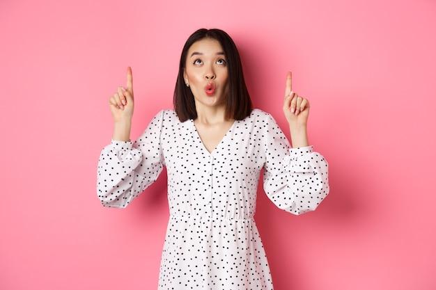 Carina ragazza coreana in un bellissimo vestito che dice wow, guardando e puntando le dita in alto, incuriosita nell'offerta promozionale, in piedi su sfondo rosa.