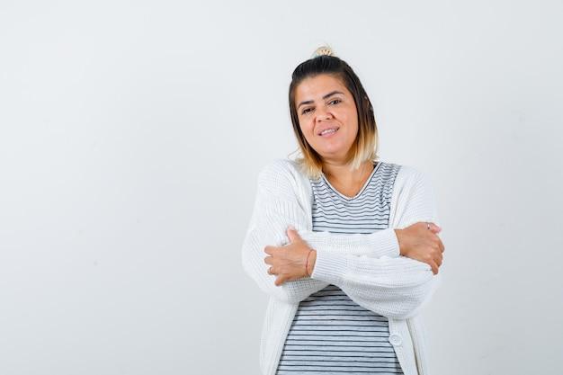 팔짱을 끼고 티셔츠, 카디건을 입고 쾌활해 보이는 귀여운 여성. 전면보기.