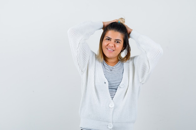 티셔츠, 카디건을 입고 머리 뒤로 손을 잡고 쾌활하게 보이는 귀여운 여성