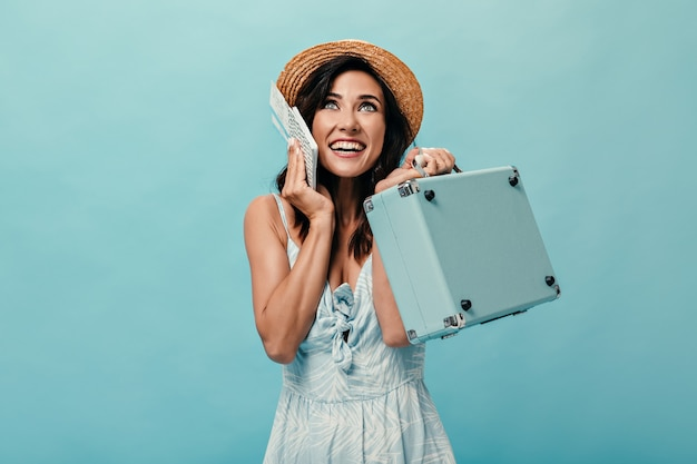 青いドレスと帽子のかわいい女性は彼女の休暇を楽しんでいて、チケット、スーツケースを持っています