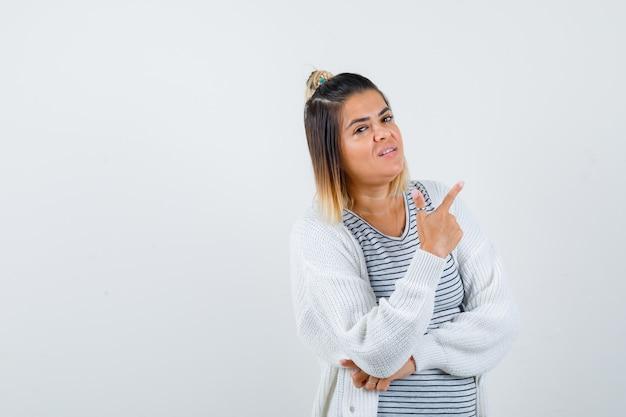 티셔츠를 입은 귀여운 여성, 가디건이 오른쪽 상단 모서리를 가리키고 자신감이 있어 보이는 전면 전망.