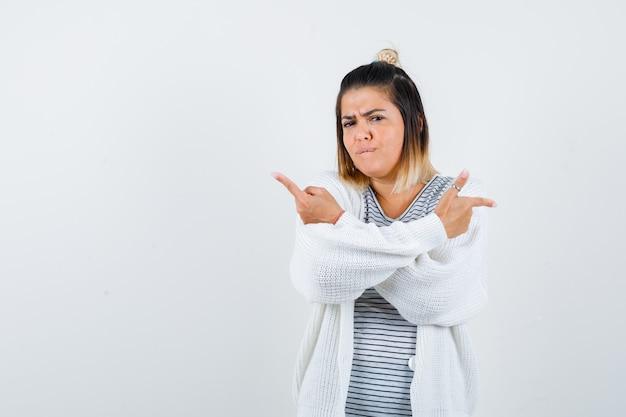 티셔츠, 카디건을 입고 좌우를 가리키며 우유부단한 표정을 짓고 있는 귀여운 아가씨. 전면보기.