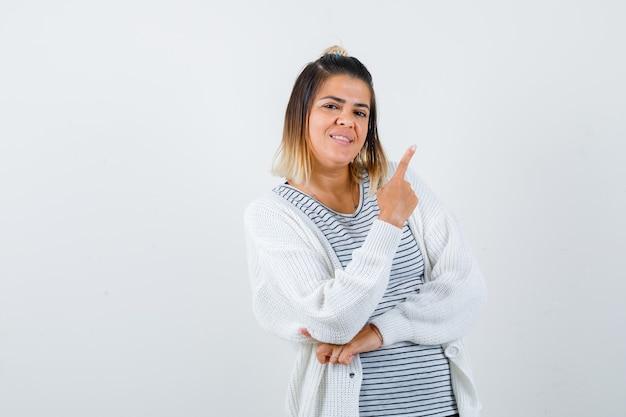 귀여운 아가씨가 티셔츠, 카디건을 가리키며 명랑한 표정을 짓고 있습니다. 전면보기.
