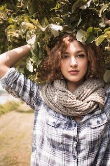 Signora carina in sciarpa sotto l'albero