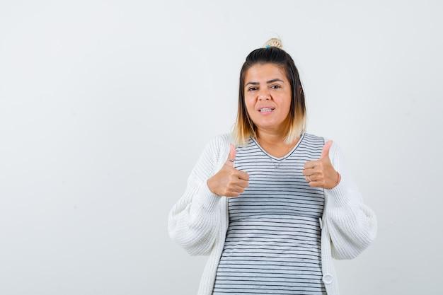 Симпатичная дама показывает двойные пальцы вверх в футболке, кардигане и выглядит довольной, вид спереди.