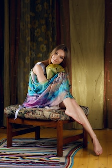Cute lady in silk scarf around her head posing on sofa with colorful fabric
