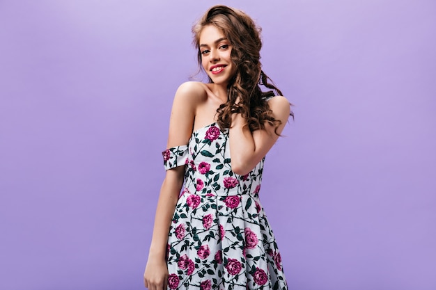 Cute lady in stylish dress looking into camera. longhaired woman in stylish summer outfit posing and smiling on purple background.