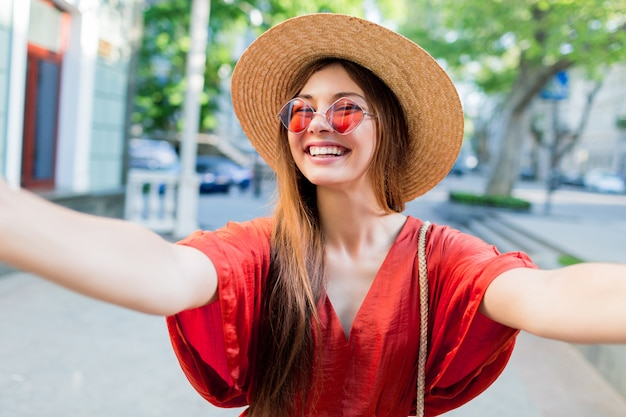 Cute lady  in stylish hat making selfie while walking outdoor in summer weekends