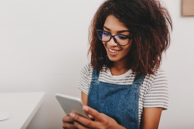 Signora carina con pelle color bronzo che controlla i nuovi messaggi nei social network usando il suo telefono